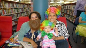Rossal dressed as a bearded lady with Cecilia holding baby Trinity dressed as clowns for Storytime.