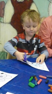 Thomas, 4, concentrates on cutting out at Storytime