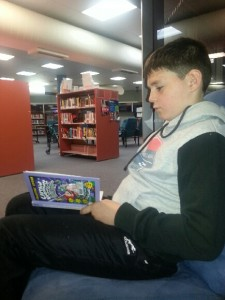 Luke Davis reads in the Library for The Reading Hour