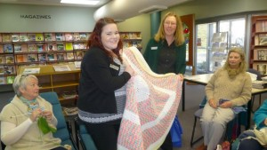 Tabitha from Housing Plus is presented with rugs by Tudi on behalf of Orange Purlers