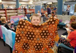 Youngest knitter Bailey with a rug he is sewing together